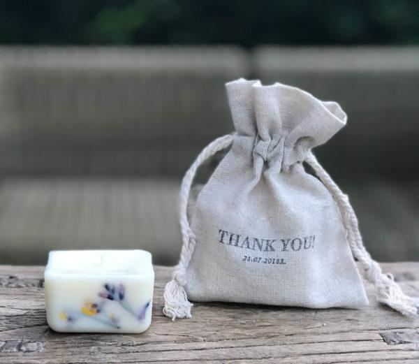 mała, sześcienna świeca naturalna z suszonymi roślinami w ściance, pakowana w lniany woreczek