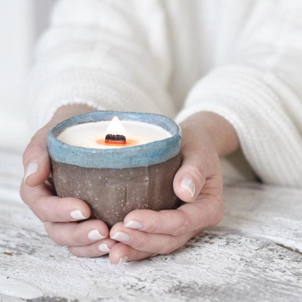 eko świeca sojowa z drewnianym knotem, w brązowej, ceramicznej miseczce z niebieskim rantem, tworzonej ręcznie
