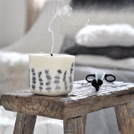 Świeca z kolekcji In Velvet o lawendowo-pomarańczowym aromacie z zatopioną w wosku suszoną lawendą.