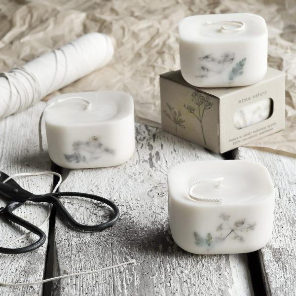 ręcznie tworzona, biała świeca z recyklingu, z suszoną rośliną w ściance, w eko kartoniku